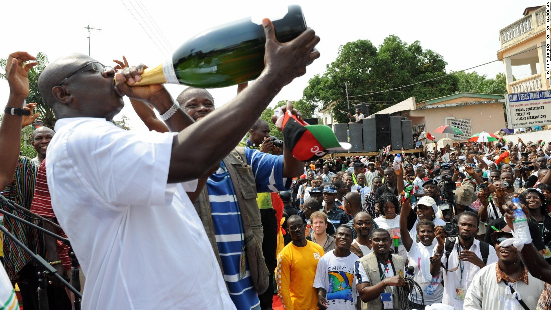 Supporters of National Democratic Congress (NDC) drink champagne and cheer to celebrate the election of President-elect John Attah Mills at his party headquarters in Accra on January 3, 2009.