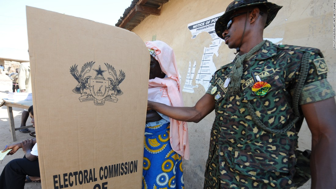 An immigration officer helps a voter at a polling station