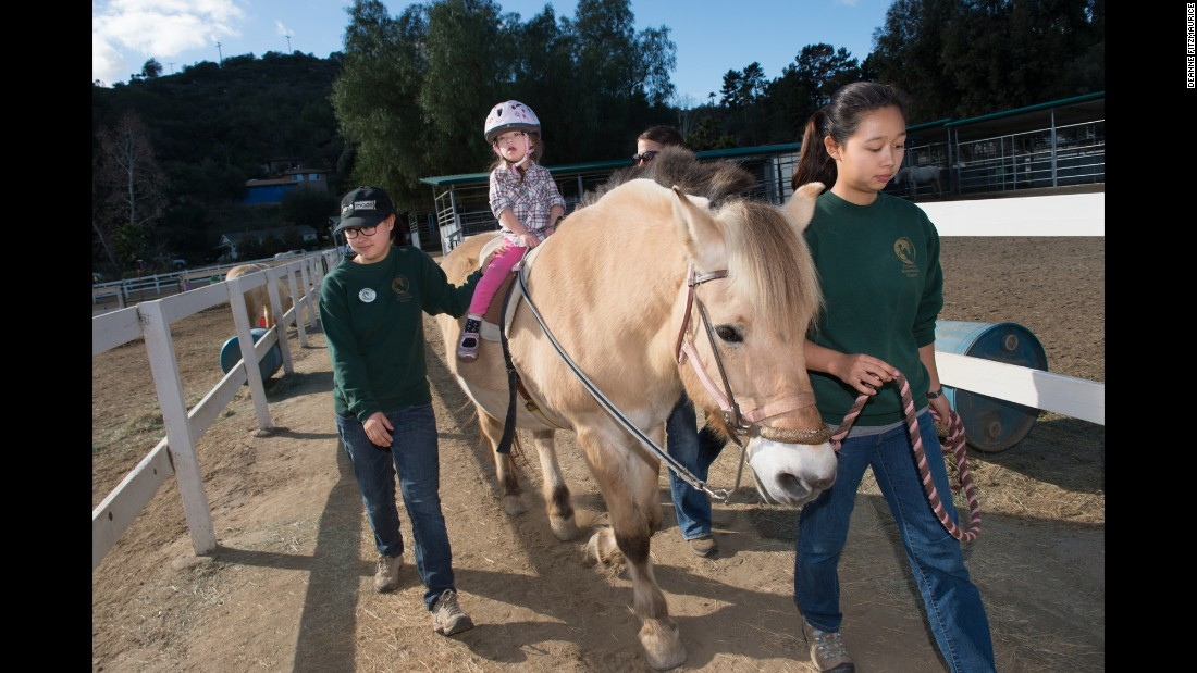 Isabella rides her favorite horse, Mary, at Reins Therapeutic Horsemanship Program in Fallbrook, California. Horse therapy has helped Isabella strengthen her muscles.