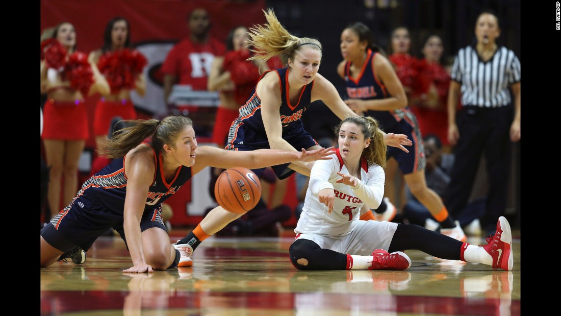 Rutgers guard Kate Hill, in white, makes a pass from the floor in the first half of an NCAA basketball game in Piscataway, New Jersey, on Saturday, December 3. Rutgers won 57-53.