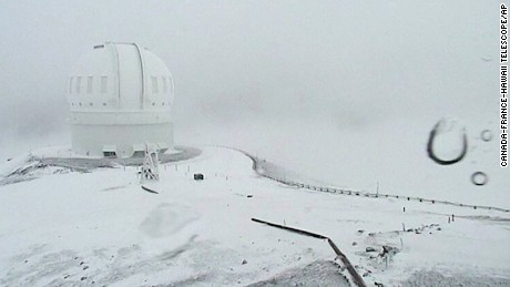 In this image made from webcam video provided by Canada-France-Hawaii Telescope, the CFHT telescope on the summit of Mauna Kea on Hawaii's Big Island is covered in snow on Thursday, Dec. 1, 2016. The National Weather Service in Honolulu has issued a winter storm warning for the summits of Hawaii's Big Island as wind and snow engulf the high peaks. (Canada-France-Hawaii Telescope via AP)