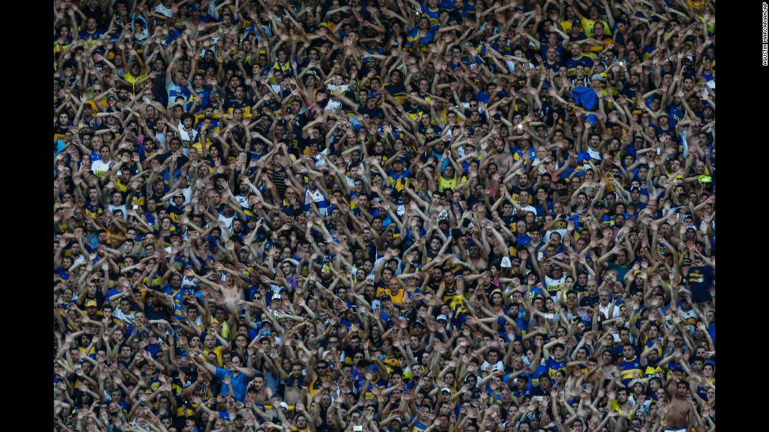 Boca Juniors soccer fans cheer for their team during an Argentine league soccer match against Racing Club in Buenos Aires on Sunday, December 4. Boca Juniors beat Racing Club 4-2.