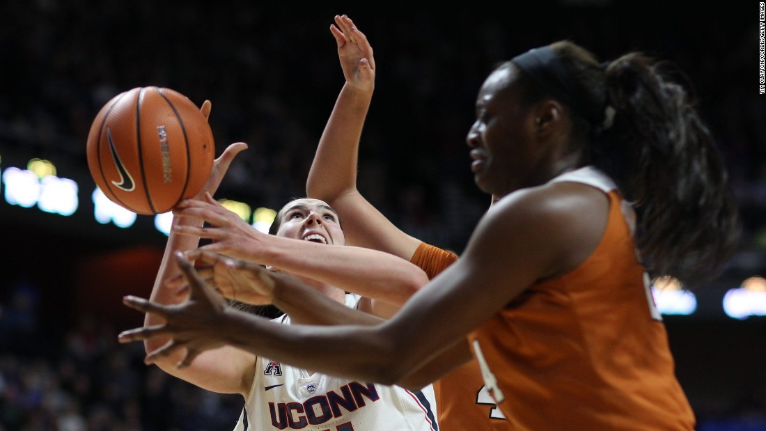 Connecticut's Natalie Butler, left, attempts a rebound against Texas' Joyner Holmes during an NCAA basketball game in Uncasville, Connecticut, on Sunday, December 4. Connecticut won their 82nd straight game, beating Texas 72-54.