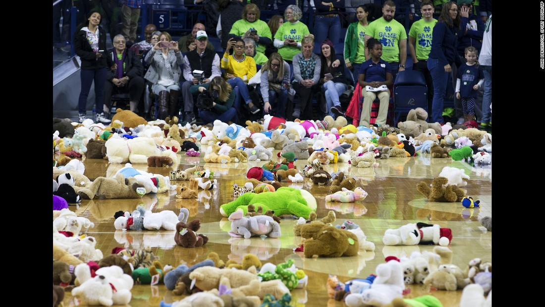People take part in the Teddy Bear Toss, a Toys for Tots charity event, during halftime at an NCAA women's basketball game between Notre Dame and Valparaiso in South Bend, Indiana, on Sunday, December 4. Notre Dame defeated Valparaiso 114-54.