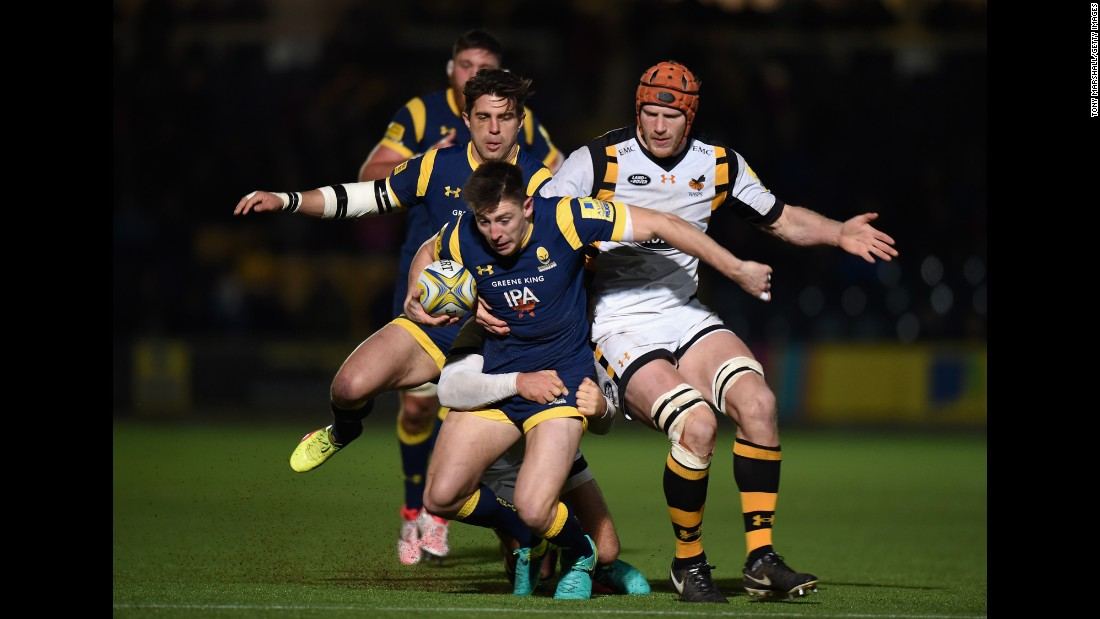 Worcester Warriors rugby player Josh Adams, in blue, is tackled by Wasps players during a match in Worcester, England, on Sunday, December 4.