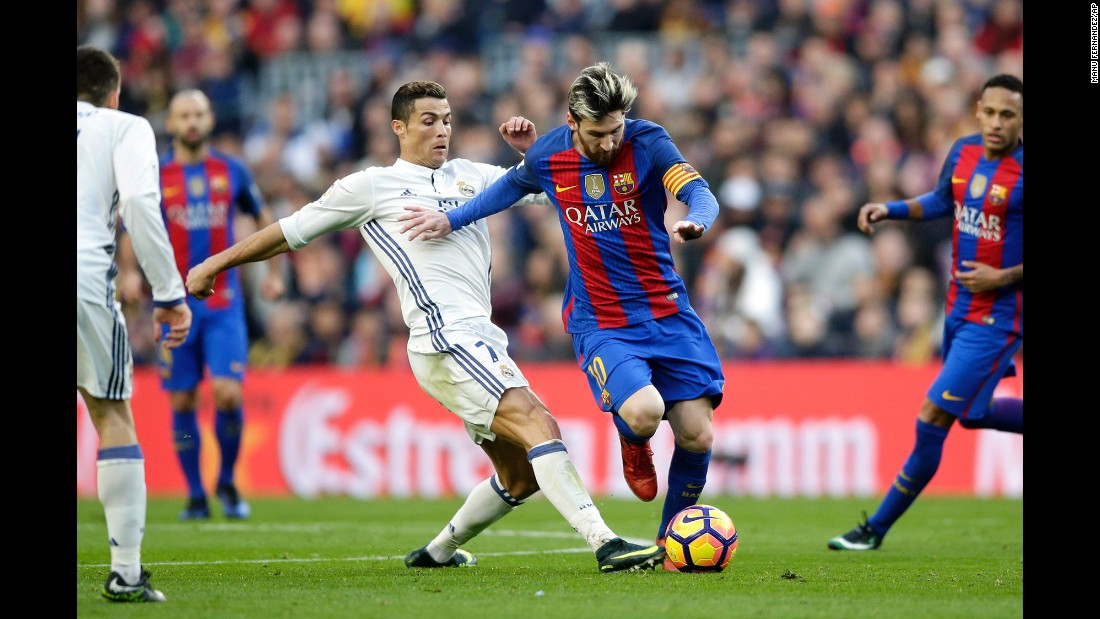 Barcelona's Lionel Messi, center right, escapes Real Madrid's Cristiano Ronaldo during a Spanish league match in Barcelona, Spain, on Saturday, December 3. The teams tied 1-1.