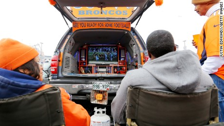 DENVER, CO - JANUARY 11: Denver Broncos fans watch football on a TV in the back of their car as they have a tail gate party outside of the venue before a 2015 AFC Divisional Playoff game between the Denver Broncos and the Indianapolis Colts at Sports Authority Field at Mile High on January 11, 2015 in Denver, Colorado.  (Photo by Justin Edmonds/Getty Images)