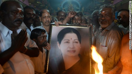 Supporters hold a photograph of Tamil Nadu state leader Jayalalithaa Jayaram as they offer prayers for her well being at a temple in Mumbai on December 5, 2016.  The ailing chief minister of southern India's Tamil Nadu state, Jayalalithaa Jayaram, who has been hospitalised for the last few months in Chennai, has suffered a cardiac arrest only days after she handed many of her responsibilities to a deputy because of illness.  / AFP / INDRANIL MUKHERJEE        (Photo credit should read INDRANIL MUKHERJEE/AFP/Getty Images)