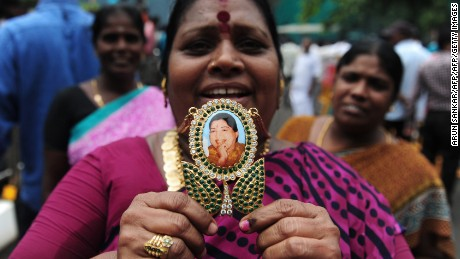A woman displays a pendant with the image of  Jayalalithaa Jayaram as they celebrate election results in front of her residence in Chennai in May, 2016.