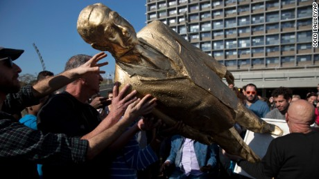 People carry a statue of Israeli Prime Minister Benjamin Netanyahu after it was placed without permit at Rabin square in Tel Aviv, Tuesday, Dec. 6, 2016. Tel Aviv residents have woken up to an unusual site: a golden statue of their prime minister featured prominently in front of City Hall. Itay Zalait, the artist behind the protest says he placed the 4.5 meter (15 foot) statue to test Israel's freedom of expression, making also a reference to the biblical golden calf, and a dig at some Israelis' idolatry of Netanyahu. (AP Photo/Oded Balilty)