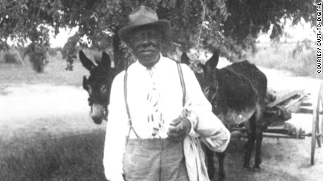 Washington Phillips, a peddler, part-time preacher and gospel singer, with his mule cart.