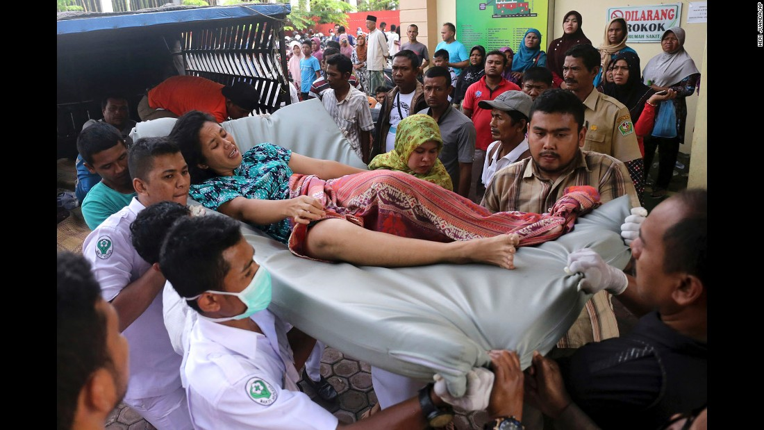 Medical personnel and family members transport a woman who was injured in the earthquake.