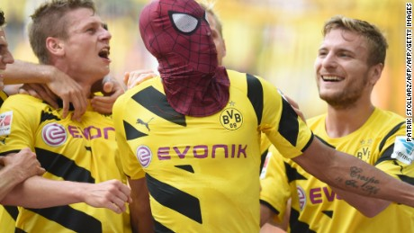 Dortmund's Italian striker Circo Immobile (R), Dortmund's Polish defender Lukasz Piszczek (L) celebrate after Dortmund's Gabonese striker Pierre-Emerick Aubameyang, who put on a Spiderman mask, scored the 2-0 goal during the German Supercup football match Borussia Dortmund vs Bayern Munich in the German city of Dortmund on August 13, 2014. AFP PHOTO / PATRIK STOLLARZ  DFL RULES TO LIMIT THE ONLINE USAGE DURING MATCH TIME TO 15 PICTURES PER MATCH. IMAGE SEQUENCES TO SIMULATE VIDEO IS NOT ALLOWED AT ANY TIME. FOR FURTHER QUERIES PLEASE CONTACT DFL DIRECTLY AT + 49 69 650050.        (Photo credit should read PATRIK STOLLARZ/AFP/Getty Images)