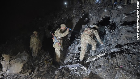 """Pakistani soldiers search for victims from the wreckage of the crashed PIA passenger plane Flight PK661 at the site in the village of Saddha Batolni in the Abbottabad district of Khyber Pakhtunkhwa province on December 7, 2016.All 48 people on board a Pakistani plane which crashed in the country's mountainous north and burst into flames have died, officials told AFP on December 7, 2016. """"No one survived,"""" said the Civil Aviation Authority spokesman. / AFP / AAMIR QURESHI        (Photo credit should read AAMIR QURESHI/AFP/Getty Images)"""