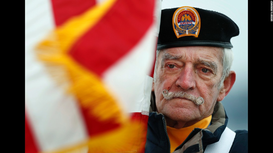 Bill Kiley, a flag bearer of the color guard, participates in a ceremony in Portland, Maine. Kiley served in the Navy from 1954-1958.