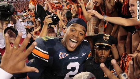 FILE - This Oct. 23, 2010, file photo shows Auburn quarterback Cameron Newton celebrating a 24-17 win over LSU at Jordan-Hare Stadium in Auburn, Ala.  The Heisman Trophy-winner added AP Player of the Year to his collection of honors, Wednesday, Dec. 22, 2010.   (AP Photo/Dave Martin, File)