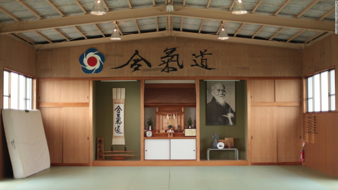 A photograph of aikido creator Morihei Ueshiba hangs on the wall at Aikido Tanabe Dojo. The blue, red and white logo is the official symbol of the International Aikido Foundation.