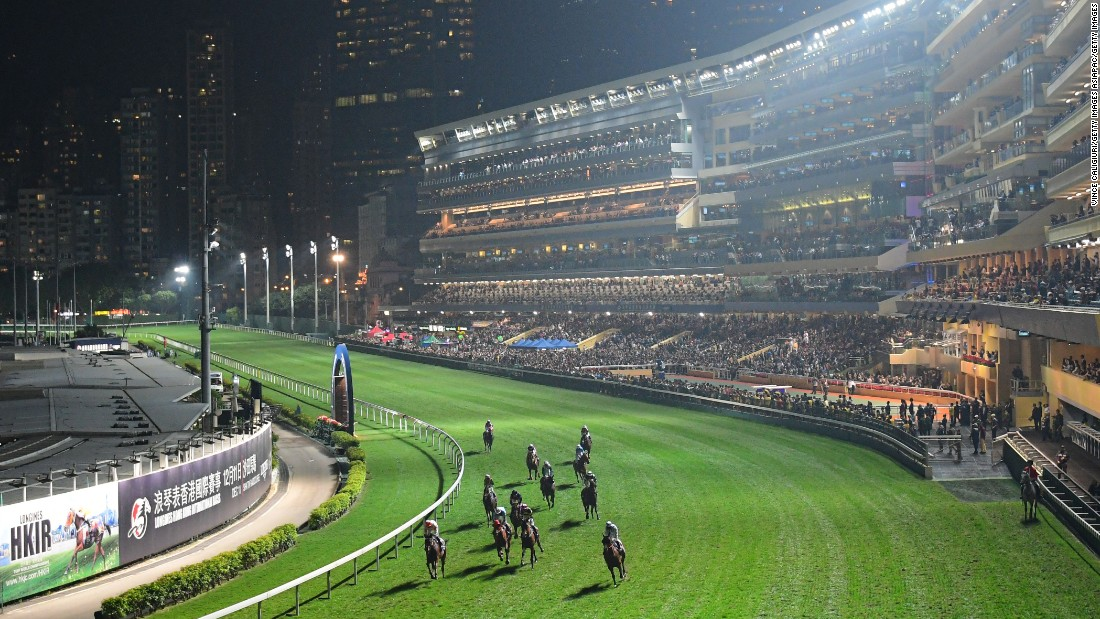 Competitors round the bend under the floodlights, with Hong Kong's skyline in the background.