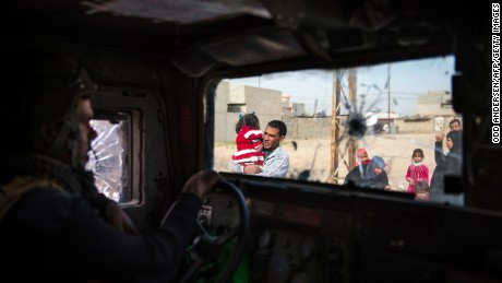 TOPSHOT - People fleeing the fighting are seen from inside an Iraqi Special Forces 2nd division Humvee in Mosul's Arbagiah neighbourhood on November 13, 2016, as they continued to battle Islamic State (IS) group forces pushing through the Arbagiah area and into the neighbourhood of Karkukli.   / AFP / Odd ANDERSEN        (Photo credit should read ODD ANDERSEN/AFP/Getty Images)