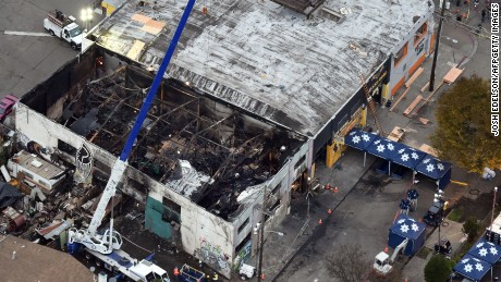 This aerial photo shows the remains of a fire ravaged warehouse on December 05, 2016 that killed at least 36 people in Oakland, California. 