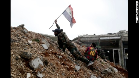 A Syrian army soldier places a Syrian national flag during a battle with rebel fighters at the Ramouseh front line, east of Aleppo, Syria, Monday, Dec. 5, 2016.