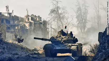 Syrian government forces drive a tank in the newly retaken area of Sahat al-Melh and Qasr al-Adly in Aleppo's Old City on December 8, 2016.