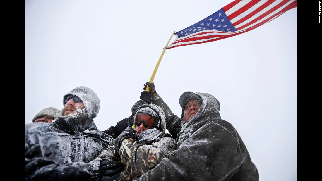 "Military veterans huddle together to hold a US flag during a march outside the Oceti Sakowin Camp in Cannon Ball, North Dakota, on Monday, December 5. Veterans from the group <a href=""http://www.cnn.com/2016/11/22/us/veterans-stand-for-standing-rock-trnd/"" target=""_blank"">""Veterans for Standing Rock""</a> arrived at the freezing Dakota Access Pipeline protest site <a href=""http://www.cnn.com/2016/12/04/us/dakota-access-pipeline-protests-veterans/"" target=""_blank"">the day before</a> in support of the Standing Rock Sioux tribe. The Army Corps of Engineers has <a href=""http://www.cnn.com/2016/12/04/politics/dakota-access-pipeline/index.html"" target=""_blank"">denied the current route for the Dakota Access Pipeline</a>, a $3.7 billion project that would cross four states and change the landscape of the US crude oil supply."