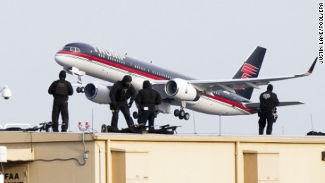 epa05666517 US President-elect Donald Trump's plane departs from LaGuardia Airport as police officers on a rooftop are seen in the foreground in New York, New York, USA, 08 December 2016.  EPA/JUSTIN LANE / POOL