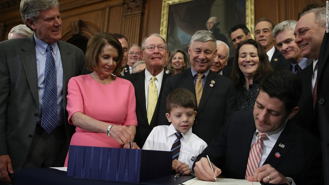 Max Schill -- a boy who suffers from a rare genetic disorder called Noonan syndrome -- watches as House Speaker Paul Ryan signs the 21st Century Cures Act at the US Capitol in Washington on Thursday, December 8. The bill, which passed 392-26, provides funding for cancer research, opioid abuse prevention and mental health treatment and aims to ease requirements of the FDA to expedite drug approvals.