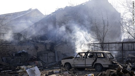 Smoke billows over a damaged car and houses near where a train derailed and exploded Saturday in northeast Bulgaria.