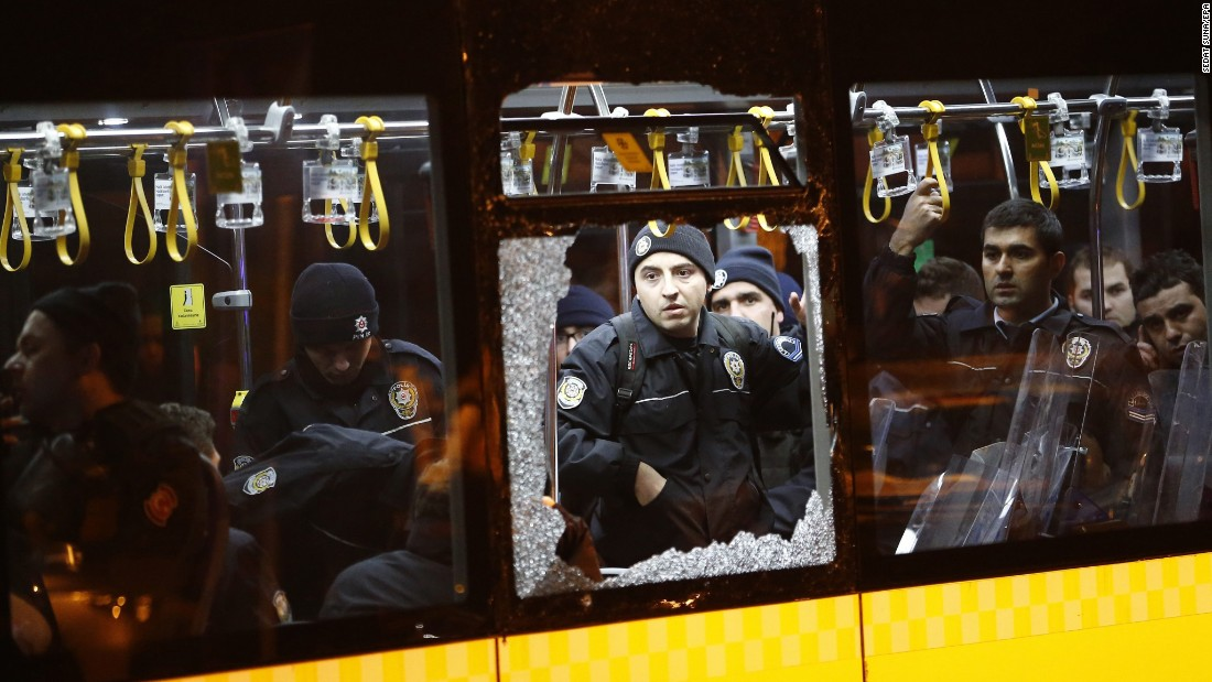 Police officers stand inside a damaged bus after an explosion.