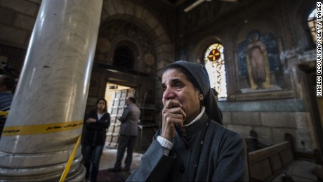A nun reacts as Egyptian security forces (unseen) inspect the scene of a bomb explosion at the Saint Peter and Saint Paul Coptic Orthodox Church on December 11, 2016, in Cairo's Abbasiya neighbourhood. The blast killed at least 25 worshippers during Sunday mass inside the Cairo church near the seat of the Coptic pope who heads Egypt's Christian minority, state media said.