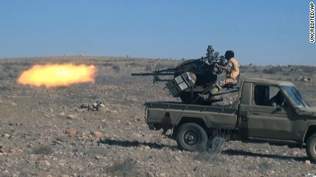 "This image posted online on Saturday, Dec. 10, 2016, by supporters of the Islamic State militant group on an anonymous photo sharing website, purports to show a gun-mounted vehicle operated by the group firing at Syrian troops, north of Palmyra city, in Homs Provence, Syria. Syrian opposition activists say the Islamic State group has regained control of the ancient town of Palmyra despite a wave of Russian airstrikes in a major advance after a year of setbacks for the group in Syria and Iraq. The Arabic caption reads, ""Targeting checkpoints of the Nussayari (derogative for Alawite Syrian) army in Jazal with heavy weapons."" (Militant Photo via AP)"