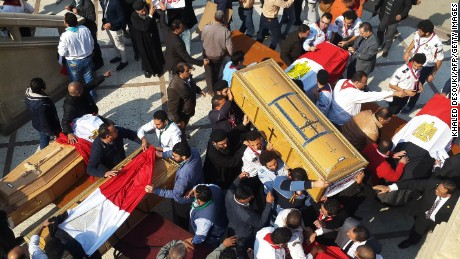 Egyptian clergymen and officials carry the coffins of the victims of the bomb explosion.