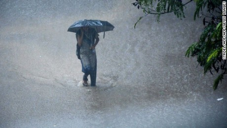 A young Indian woman walks under an umbrella through floodwaters in Chennai on December 1, 2015, during a downpour of heavy rain in the southern Indian city.