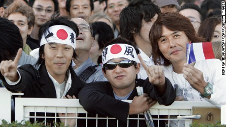 Paris, FRANCE:  Japanese support the horse, Deep Impact and his jockey Yutake Take of Japan which attract a huge fan club, during the Prix de l'Arc de Triomphe's race at Longchamp, 01 October 2006 in Paris.  Around 5,000 Japanese nationals had travelled over to Longchamp, in western Paris to see the five-year-old colt take on Europe's finest including last year's champion Hurricane Run but that did not deter them from queuing up at a specially designated betting stall solely for Japanese punters. AFP PHOTO BERTRAND GUAY  (Photo credit should read BERTRAND GUAY/AFP/Getty Images)