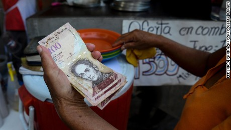 "A woman pays with 100-bolivar-bills at a fast food restaurant at Catia neighbourhood in Caracas on December 12, 2016. Venezuelan President Nicolas Maduro on Sunday signed an emergency decree ordering the country's largest banknote, the 100 bolivar bill, taken out of circulation to thwart ""mafias"" he accused of hoarding cash in Colombia. / AFP / Federico PARRA        (Photo credit should read FEDERICO PARRA/AFP/Getty Images)"