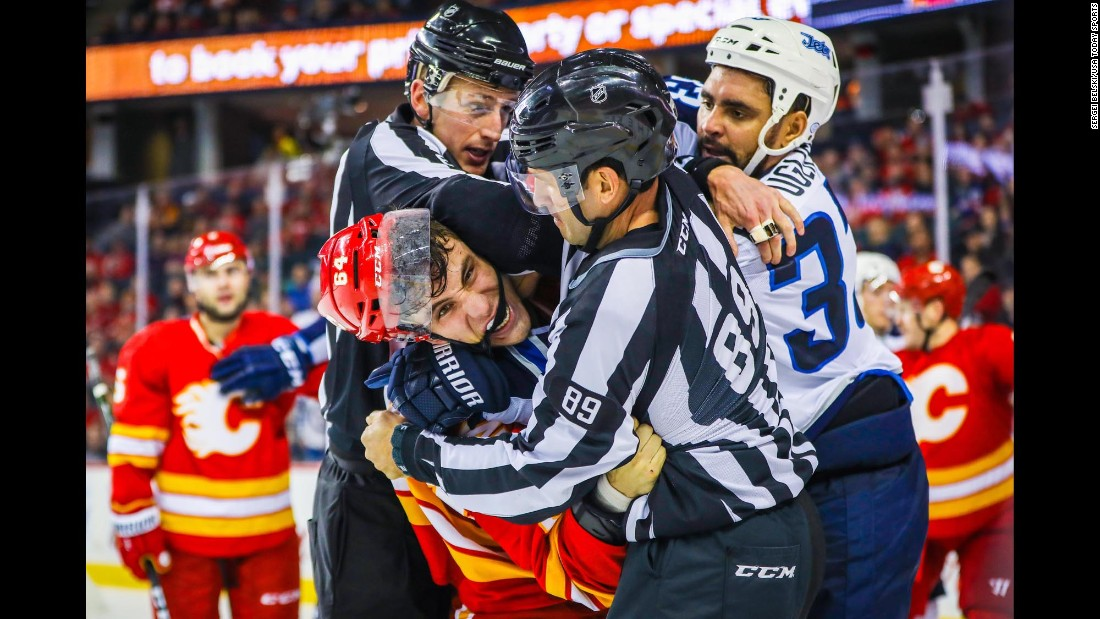 NHL officials break up Calgary's Garnet Hathaway, left, and Winnipeg's Dustin Byfuglien on Saturday, December 10.