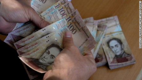 "A man counts 100-bolivar-bills at an office in Caracas on December 12, 2016.  Venezuelan President Nicolas Maduro on Sunday signed an emergency decree ordering the country's largest banknote, the 100 bolivar bill, taken out of circulation to thwart ""mafias"" he accused of hoarding cash in Colombia. / AFP / FEDERICO PARRA        (Photo credit should read FEDERICO PARRA/AFP/Getty Images)"