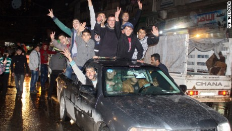 Citizens celebrate on the streets of Aleppo on Monday after regime forecs recaptured the al-Sheik Saeed and al-Sukkari neighborhoods.