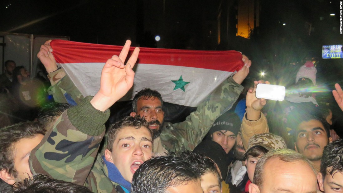 Syrians celebrate in a government-held district of Aleppo on Monday, December 12.
