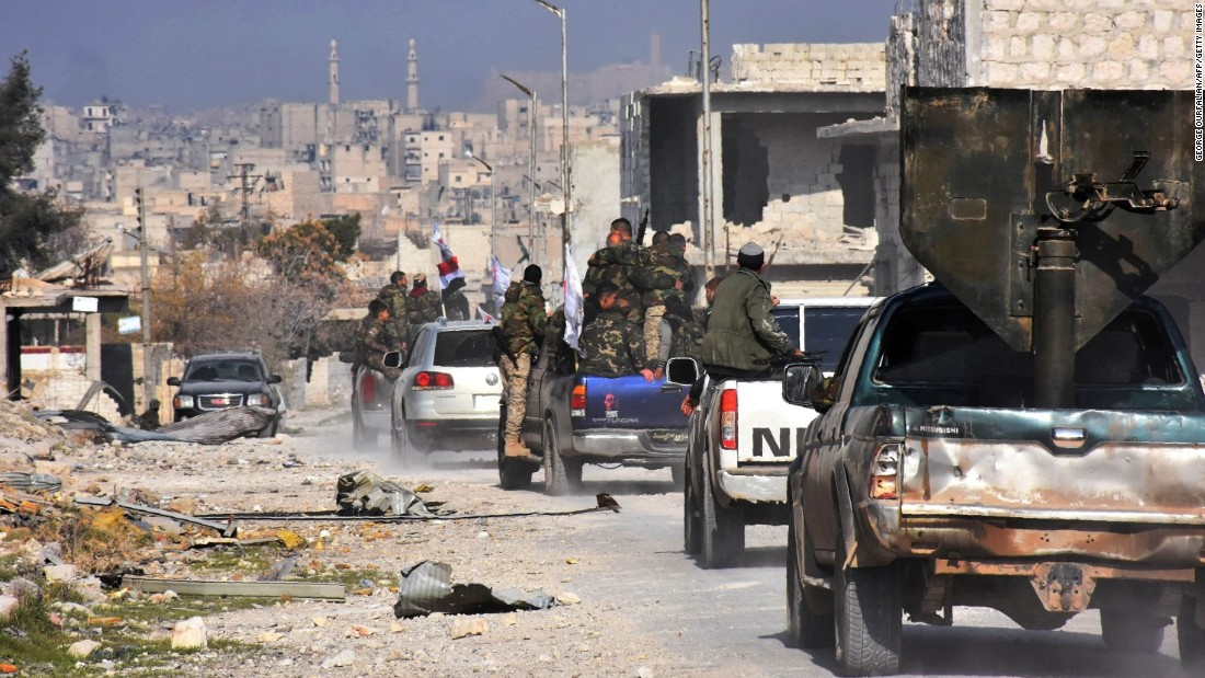 Pro-government forces patrol Aleppo's Sheikh Saeed district on December 12 after it was recaptured from rebel forces.