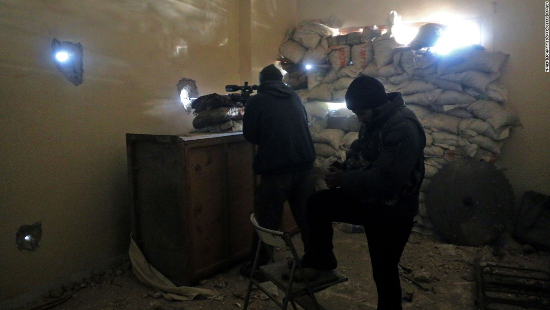 Rebel fighters take aim at pro-government positions in Aleppo on Friday, December 9.