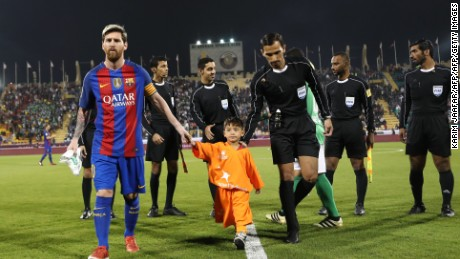 FC Barcelona Lionel Messi (L) holds the hands of Afghan boy Murtaza Ahmadi on the pitch before the start of a friendly football match against Saudi Arabia's Al-Ahli FC on December 13, 2016 in the Qatari capital Doha.  Barcelona play Saudi champions Al-Ahli in a friendly in Doha, the Spanish club's last major obligation of its four year shirt sponsorship deal with Qatar Airways.   / AFP / KARIM JAAFAR        (Photo credit should read KARIM JAAFAR/AFP/Getty Images)