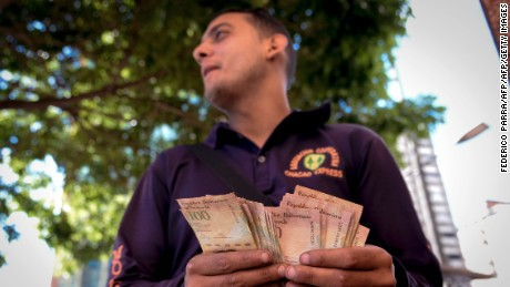 "A man counts 100-Bolivar-bills in a street in Caracas on December 13, 2016.   Venezuelan President Nicolas Maduro ordered on December 12 the border with Colombia sealed for 72 hours, accusing US-backed ""mafias"" of conspiring to destabilize his country's economy by hoarding bank notes. The closure came a day after Maduro signed an emergency decree removing Venezuela's largest bank note, the 100 bolivar bill, from circulation because of what he called a Washington-sponsored plot against his country's troubled economy. / AFP / FEDERICO PARRA        (Photo credit should read FEDERICO PARRA/AFP/Getty Images)"