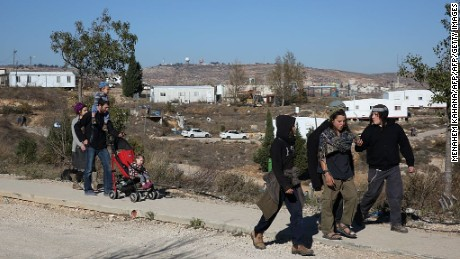 Israeli settlers walk in the outpost of Amona in the West Bank on December 9, 2016.