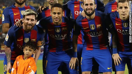 TOPSHOT - Afghan boy Murtaza Ahmadi poses for a picture with the FC Barcelona team: (top L to R) Rafinha, Javier Mascherano, André Gomes, Ivan Rakitic, Gerard Piqué, Ter Stegen (bottom L to R) Lionel Messi, Neymar Junior, Paco Alcácer, Lucas Digne, Luis Suárez , on the pitch before the start of a friendly football match against Saudi Arabia's Al-Ahli FC on December 13, 2016 in the Qatari capital Doha.  Barcelona play Saudi champions Al-Ahli in a friendly in Doha, the Spanish club's last major obligation of its four year shirt sponsorship deal with Qatar Airways.   / AFP / KARIM JAAFAR        (Photo credit should read KARIM JAAFAR/AFP/Getty Images)