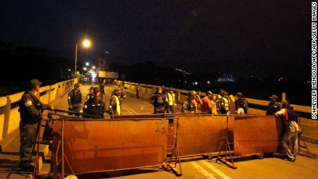 "TOPSHOT - Venezuelan National Guard personnel stand guard behind a barrier on the Simon Bolivar bridge on the Colombian border with Venezuela, on December 12, 2016. Venezuelan President Nicolas Maduro on Monday ordered the border with Colombia sealed for 72 hours, accusing US-backed ""mafias"" of conspiring to destabilize his country's economy by hoarding bank notes. The closure came a day after Maduro signed an emergency decree removing Venezuela's largest bank note, the 100 bolivar bill, from circulation because of what he called a Washington-sponsored plot against his country's troubled economy. / AFP / SCHNEYDER MENDOZA        (Photo credit should read SCHNEYDER MENDOZA/AFP/Getty Images)"