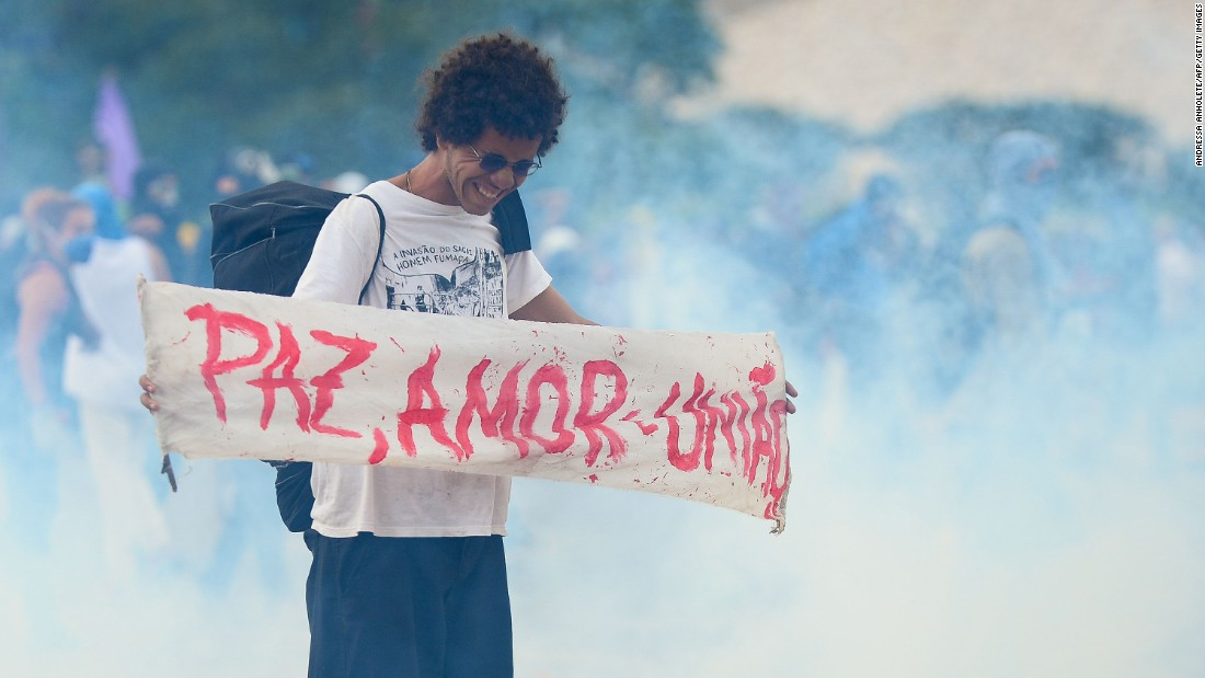 "A demonstrator holds a sign that reads, ""peace, love, and unity,"" in the midst of a clash between protesters and police outside the National Congress in Brasilia on December 13."