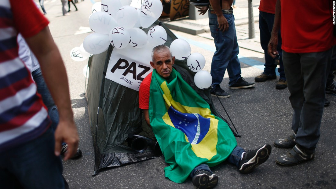A demonstrator sits wrapped in a Brazilian flag outside the state legislature in Rio de Janeiro on December 13, where police, firefighters, and teachers gathered for the rally.